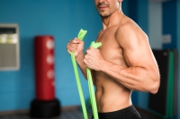 Man exercising with resistance band in gym