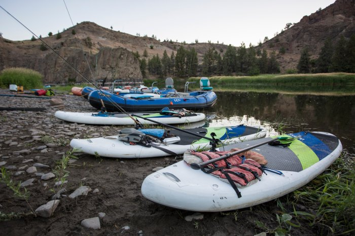 SUPs and rafts wait on the edge of a river.