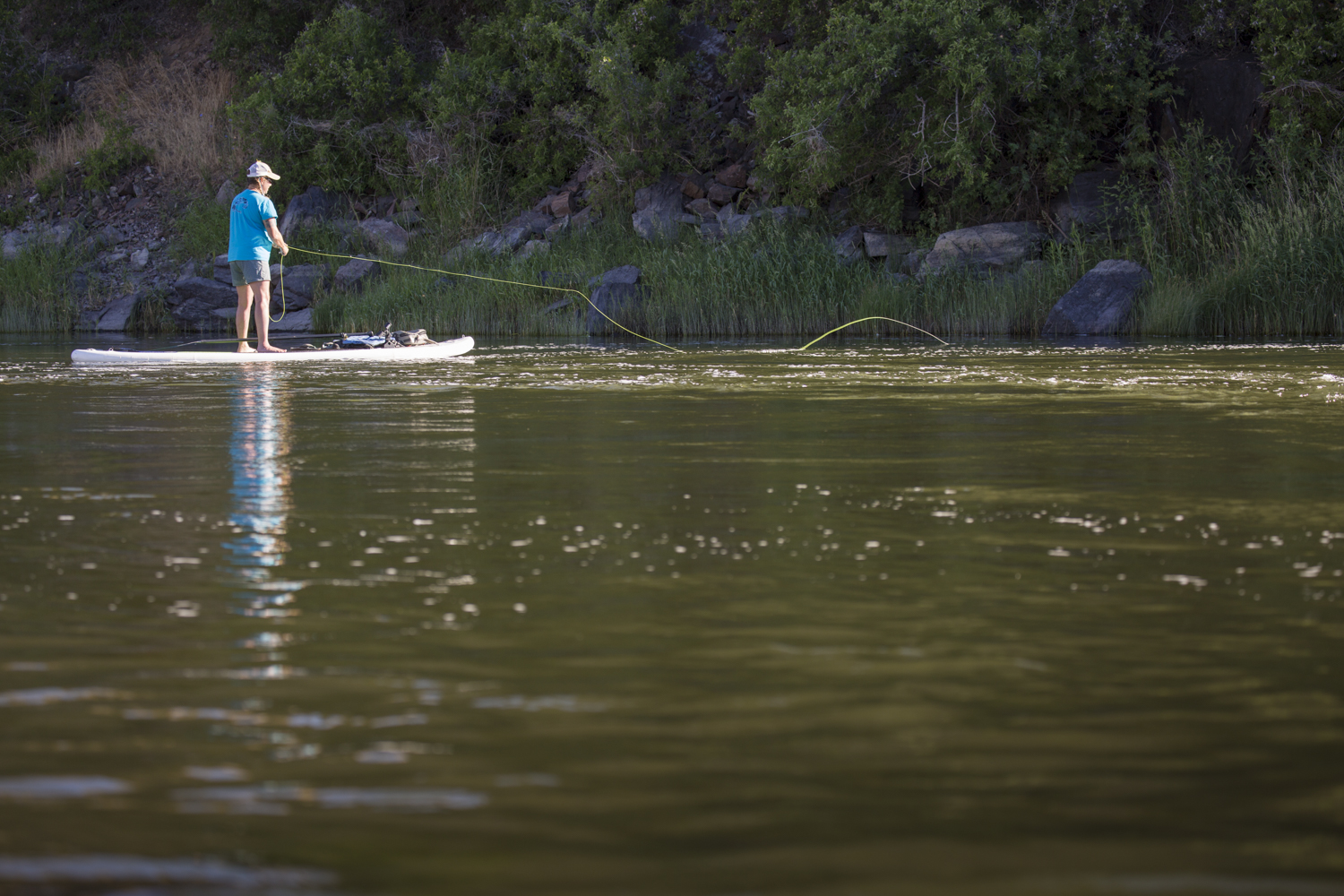 Woman fly-fishing from SUP on Oregon's John Day River.