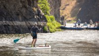 Woman fishing from SUP meeting rafts on the river.
