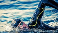 Male swimming in wetsuit