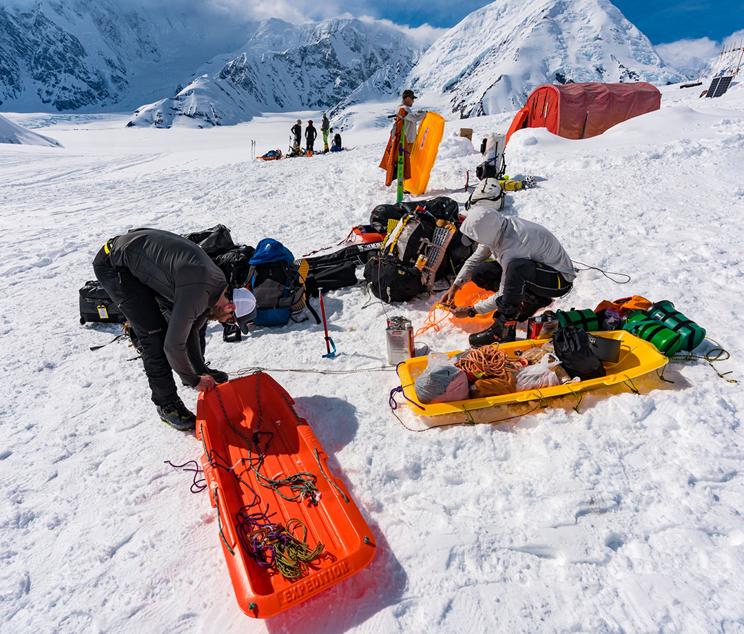 Mike Chambers, Jason Antin, and Will Seeber packing sleds with gear