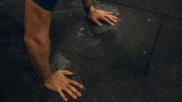 Man doing burpees on a gym floor
