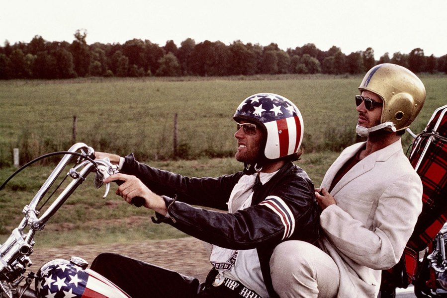 Peter Fonda, wearng a stars-and-stripes helmet, and Jack Nicholson, wearing a gold American football helmet, as they ride Fonda's chopper motorcycle in a publicity still issued for the film, 'Easy Rider', USA, 1969. The film, directed by Dennis Hopper, starred Fonda as 'Wyatt', and Nicholson as 'George Hanson'. (Photo by Silver Screen Collection/Getty Images)