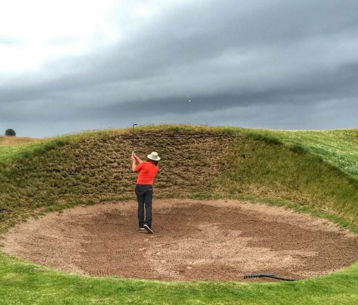 The author playing a shot from one of the twin Spectacles bunkers at Carnoustie