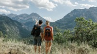 Two hikers wearing United By Blue bags