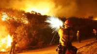 CALIMESA, CA - OCTOBER A U.S. Forest Service firefighter uses a pistol to fire flares into brush to set a backfire to control the Woodhouse fire, also being called the Calimesa fire, in San Timoteo Canyon on October 6, 2005 near Calimesa, in Riverside County, California. The wildfire spread to about 6,400 acres since it began yesterday afternoon threatening 100 homes. A break in the strong dry Santa Ana winds during the night helped firefighters create containment lines around 25 percent of the fire. (Photo by David McNew/Getty Images)
