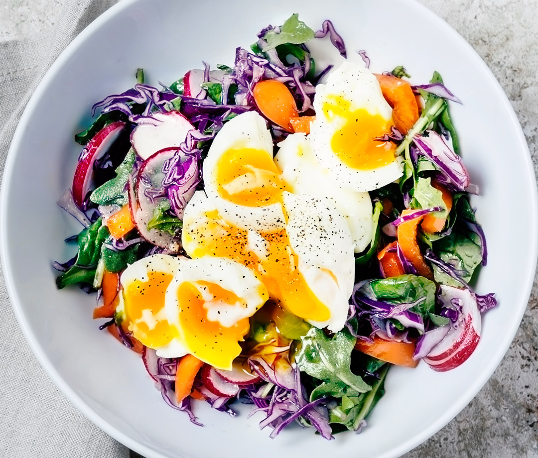 An example of a paleo diet meal: a fresh salad with soft-boiled eggs