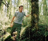 Young man hiking through forest