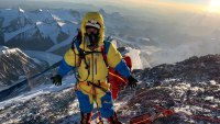 Rob Lea stands on the summit of Mount Everest
