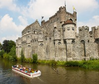 """Tour boats passing the Gravensteen, or """"Castle of the Counts,"""" a medieval castle doubling as a weapons museum in Ghent, Belgium"""
