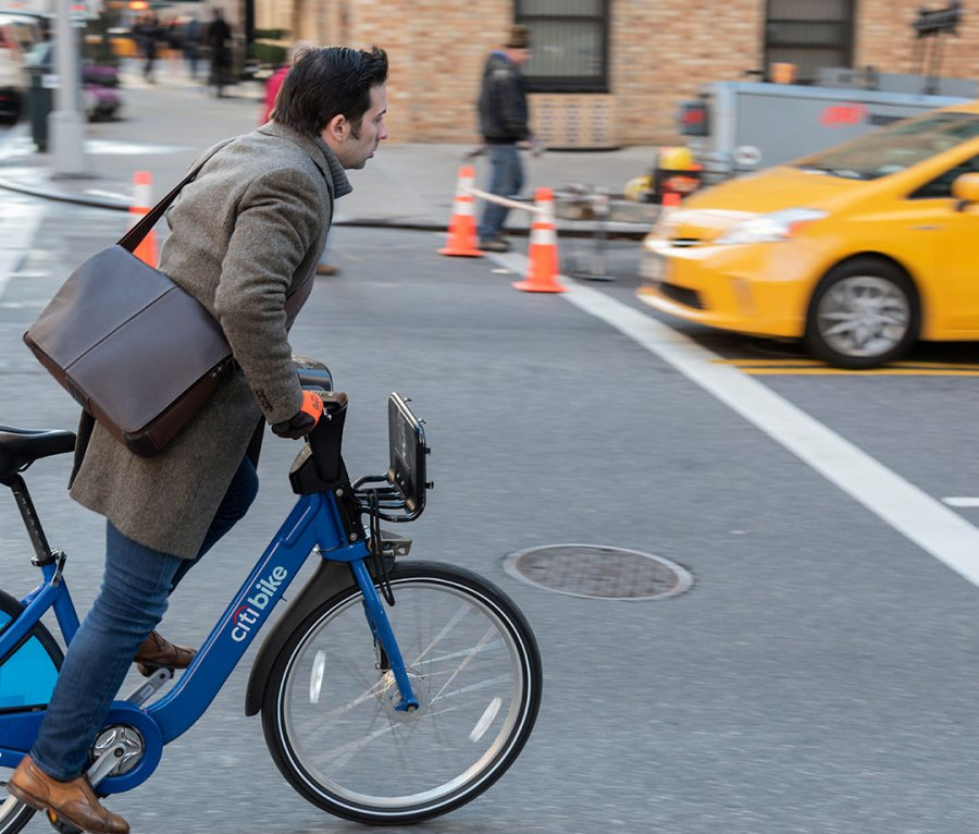 A businessman riding a Citi Bike to work in New York City, NY