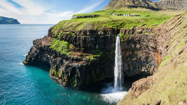 Gasadalur in the background of a waterfall on the Faroe Islands, Denmark