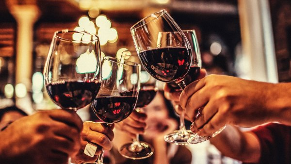 People clinking glasses of red wine