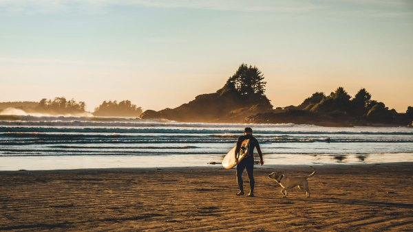 Surfer with his dog on Cox Bay beach, Tofino, British Columbia