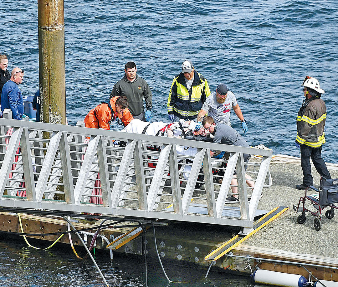 Emergency workers transport an injured person after the midair crash in May.