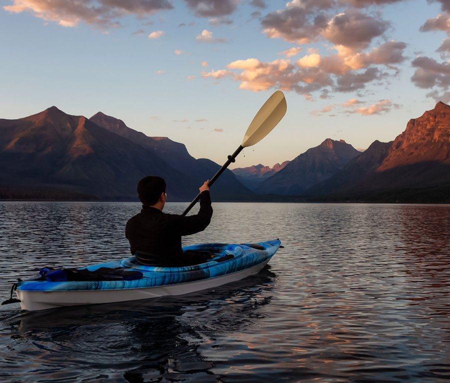Kayaking across Lake McDonald in Glacier National Park in Montana with the Rockies looming in the background