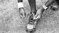 Man tying running shoes lace in the park outdoor.