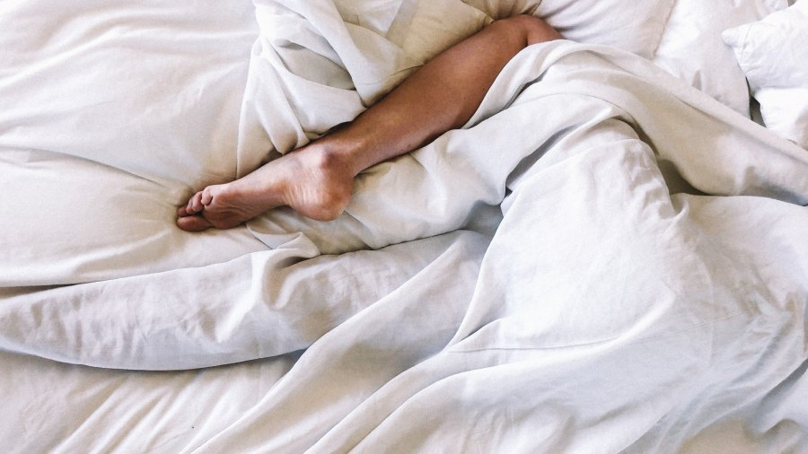 Woman's leg in messy bed sheets