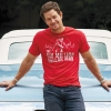 """Mark Wahlberg wears a red """"Six Million Dollar Man"""" T-shirt by Amazon, jeans by Hudson Jeans, sneakers by Jordans, and a watch by Patek Philippe"""