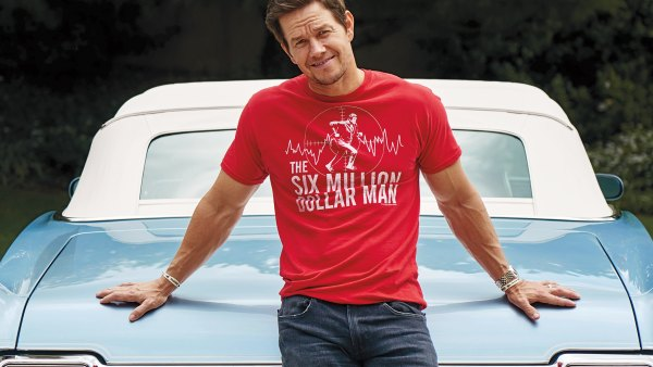 "Mark Wahlberg wears a red ""Six Million Dollar Man"" T-shirt by Amazon, jeans by Hudson Jeans, sneakers by Jordans, and a watch by Patek Philippe"