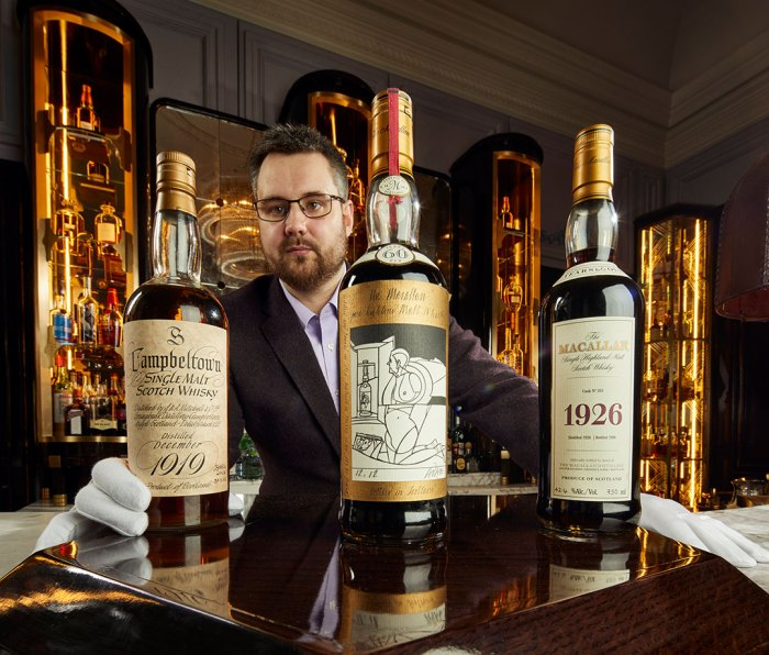 Whisky Auctioneer founder Iain McClune with bottles of Springbank and Macallan