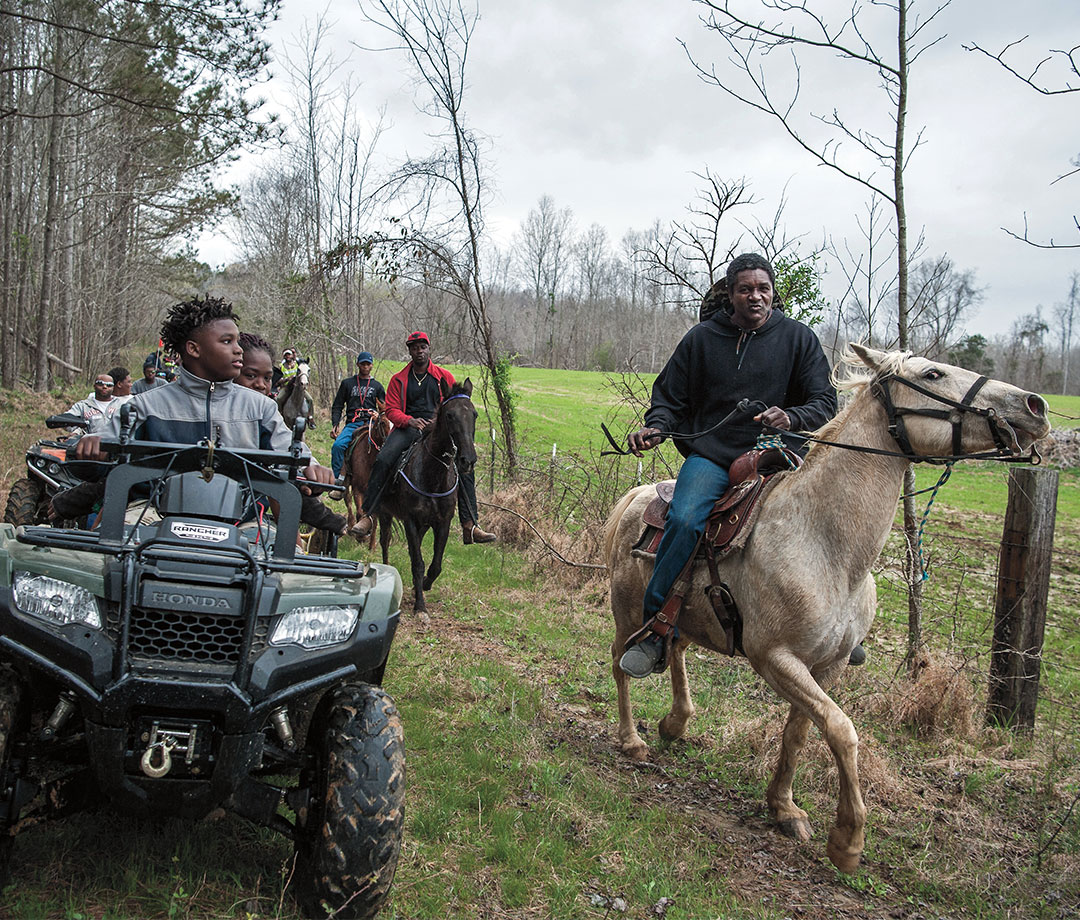 Wrenn (far right) and a group of Hill Riders hit the trail, as kids keep pace with four- wheelers.