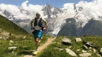 Man running on a trail surrounded by mountains