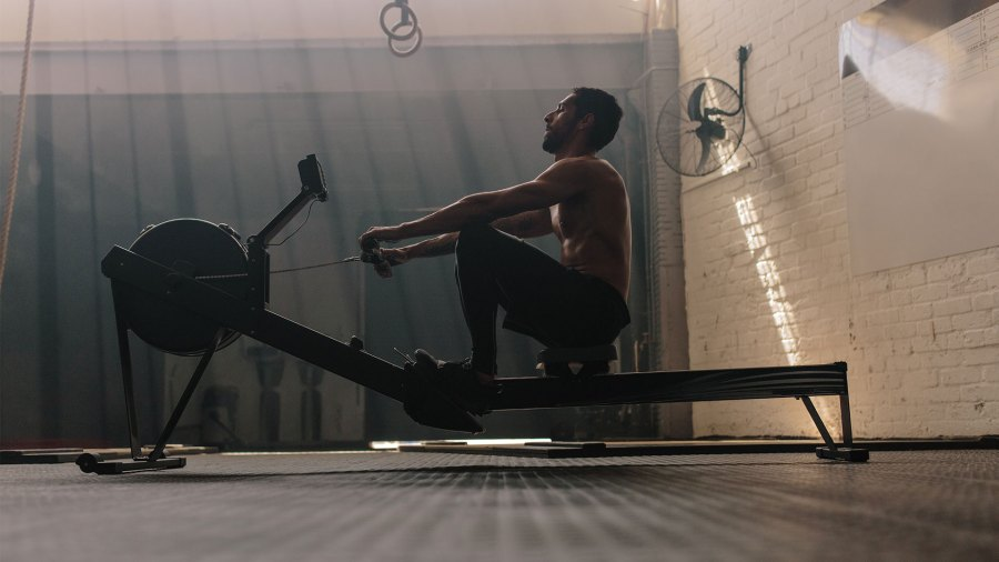 Muscular male using rowing machine in gym.