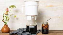 Woman pouring freshly made cold brew into glass from Toddy Cold Brew System carafe