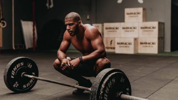 Man kneeling in front of barbell in gym