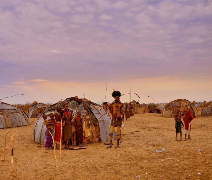 A family in the Dassanech tribe outside their home