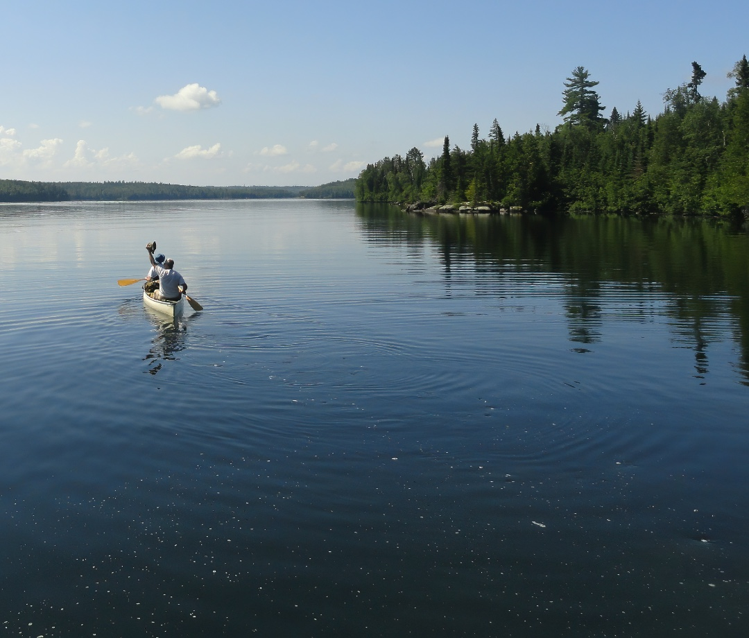 People in a Canoe Wave Goodbye to the Shore in the Boundary Waters Canoe Area Wilderness, Minnesota, USA