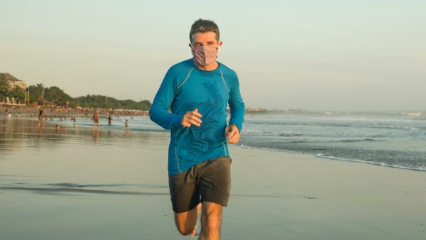 Man running on the beach with mask
