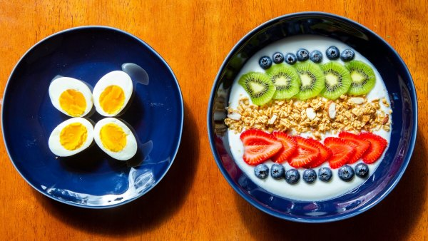 Breakfast of hard boiled eggs and yogurt with blueberries, kiwis, strawberries, and granola