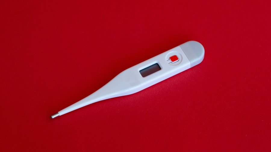 Cinical thermometer on red backdrop
