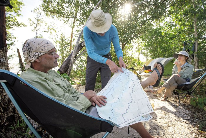 At the Graveyard Creek backcountry campsite, the author studies a map while Greg Bellware traces a route and Robin Deykes listens.