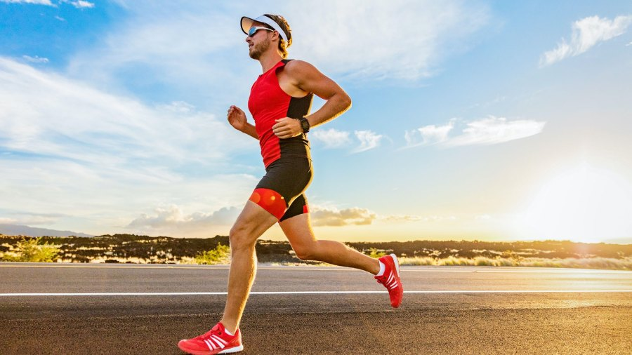 Male triathlete running on the open road