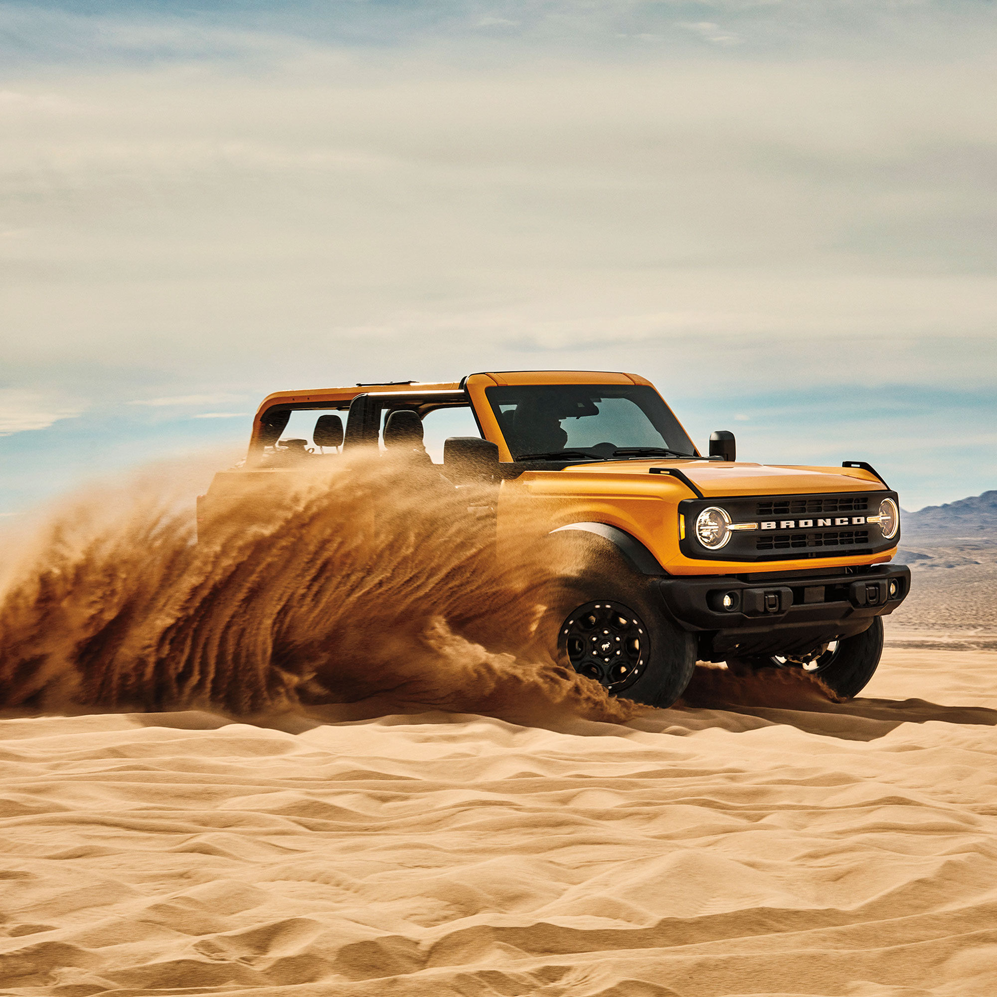 Ford Bronco tearing through sand in desert