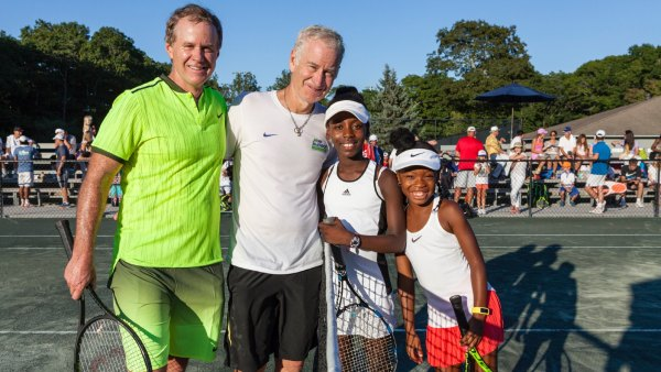 John McEnroe posing with brother Patrick McEnroe and youth tennis players at John McEnroe Tennis Academy