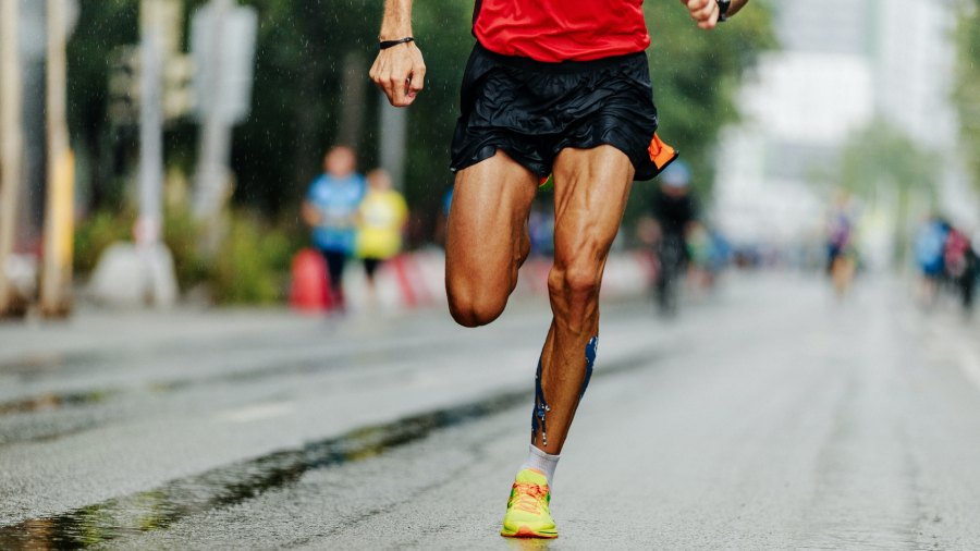 Man running through rainy city streets during triathlon