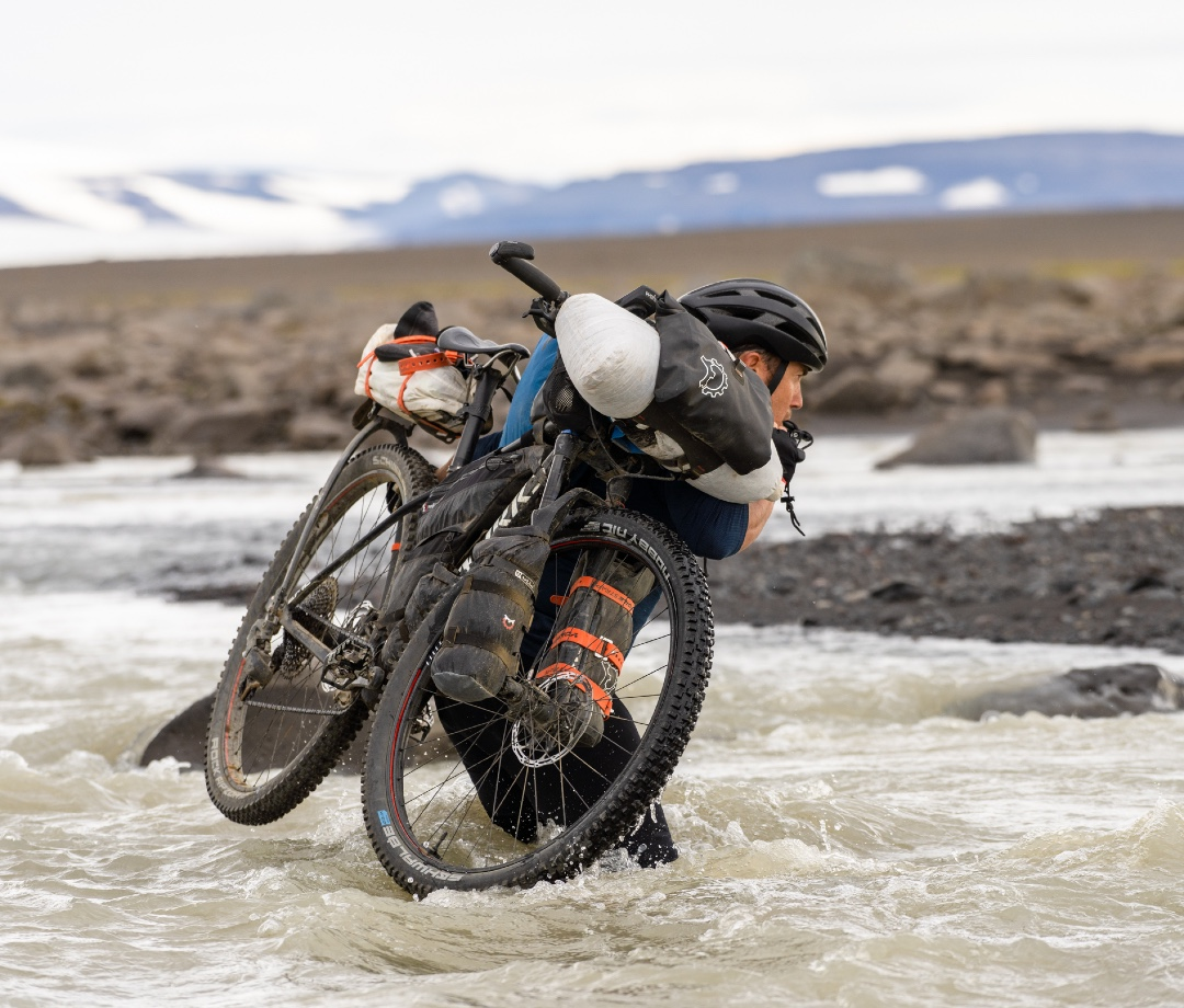 Chris Burkard carrying his bike and gear across a river.