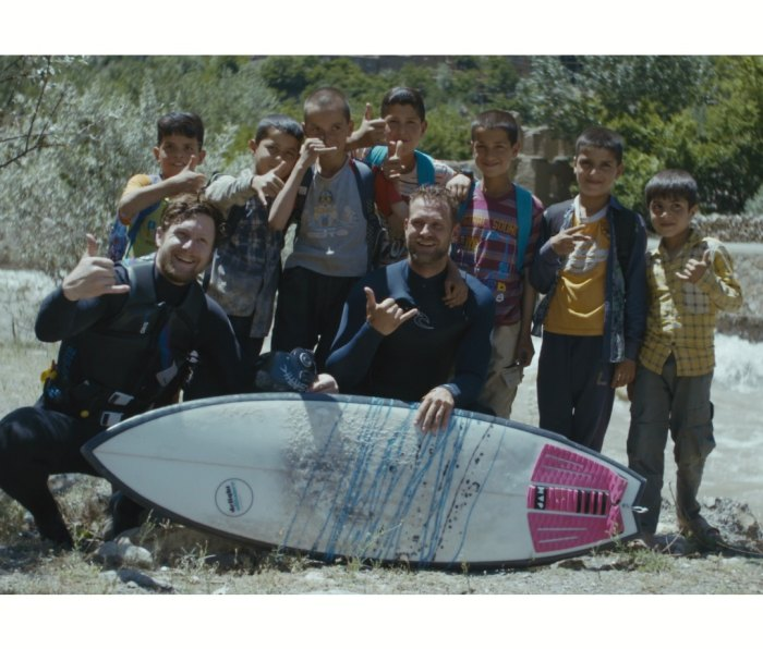 Jacob Kelly Quinlan poses with local kids after surfing a river in Afghanistan