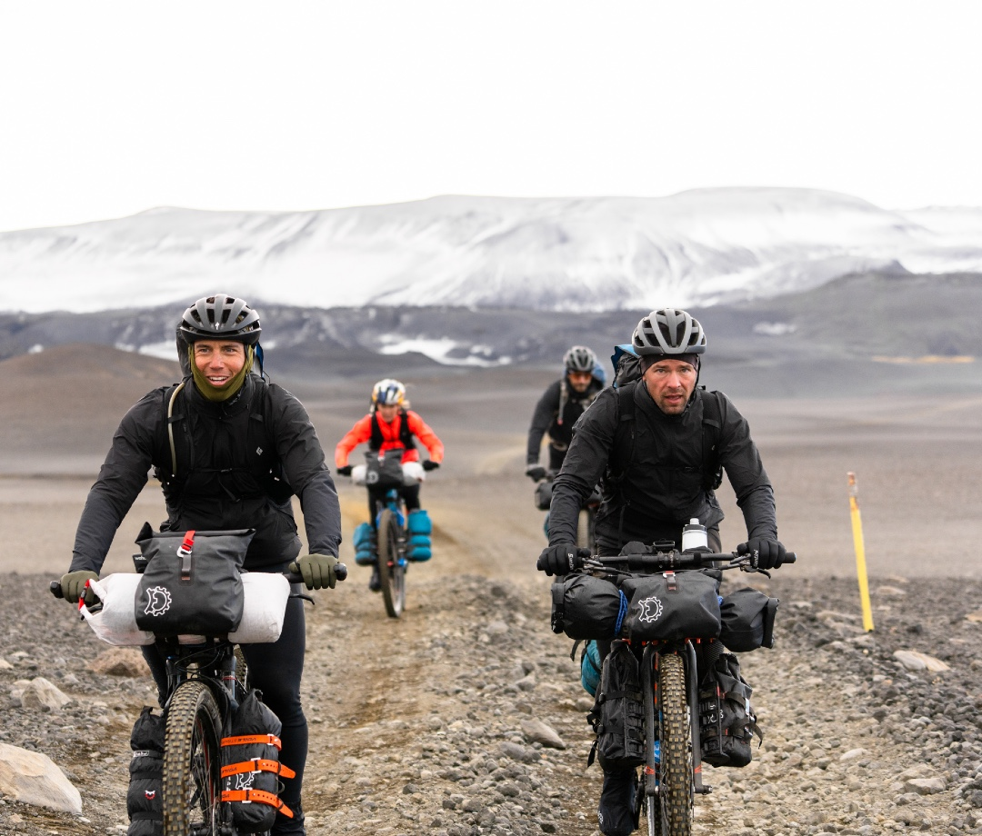Chris Burkard, Emily Batty, Adam Morka, and Eric Batty biking with glaciers in the background.
