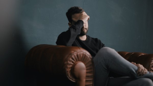 Man sitting alone on couch covering eyes with hand