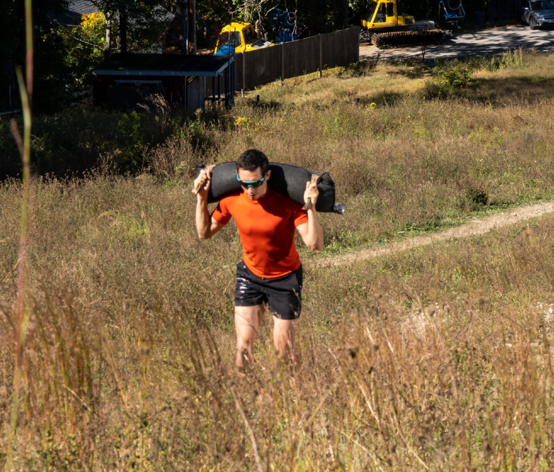 OCR athlete Ryan Kempson doing weighted hill run with sandbag on shoulders