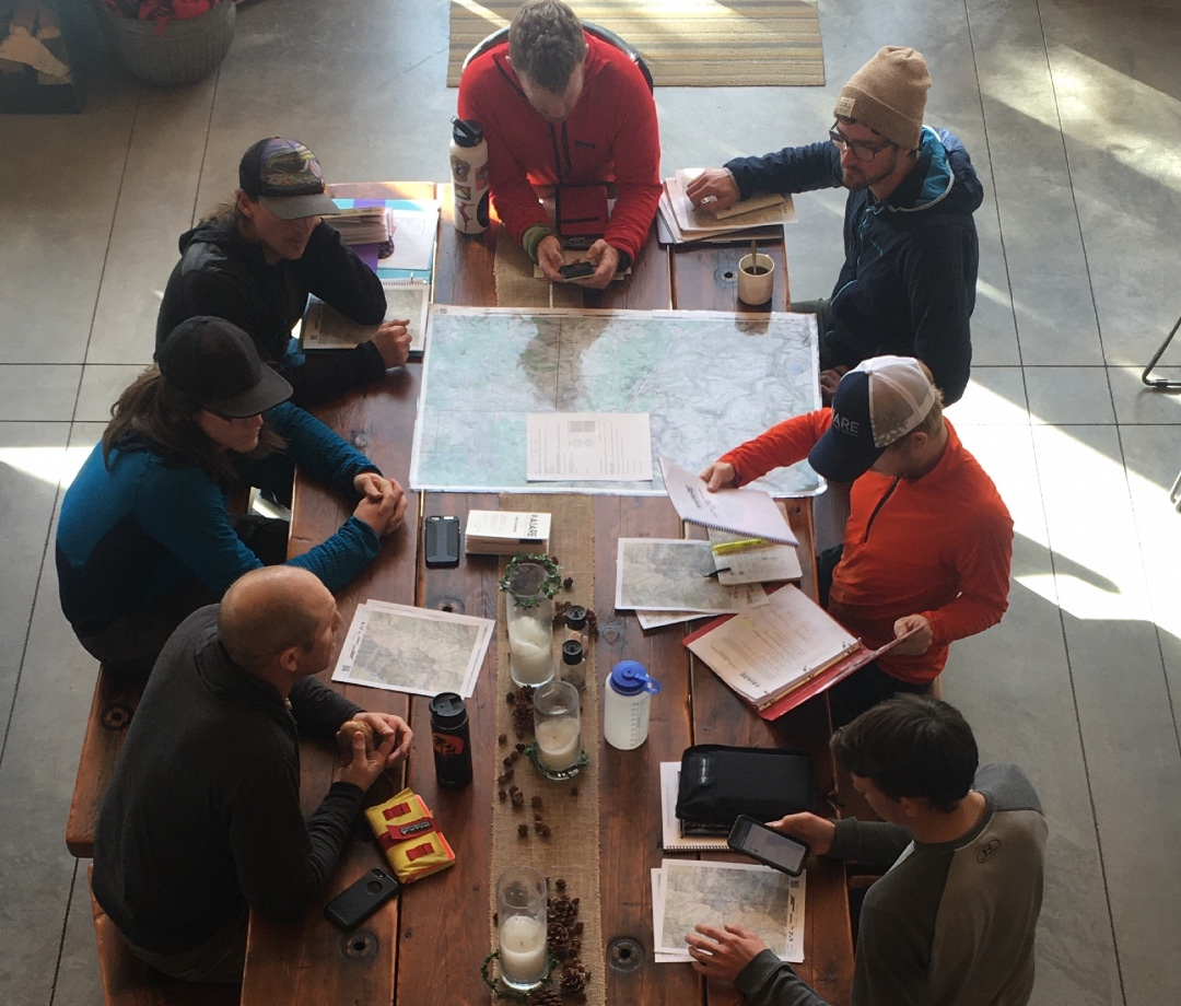 Adventurers reviewing avalanche safety education and protocols