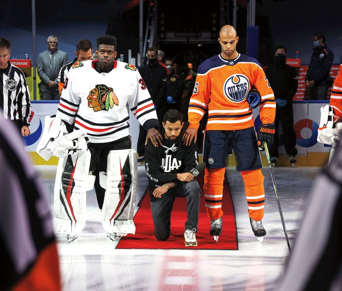 Between Blackhawks goalie Malcolm Subban and Oilers defenseman Darnell Nurse, Dumba kneels for the national anthem after his Aug. 1 playoffs speech.