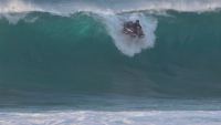 Jamie O'Brien surfing Pipeline on a blow-up raft.