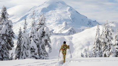 Person in colorful ski kit backcountry skiing in Washington with Mt. Baker in the background